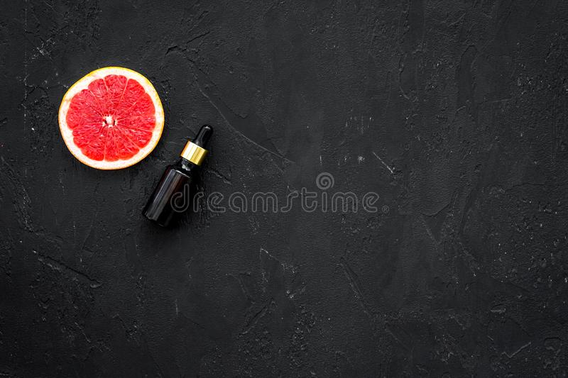 Organic cosmetic with grapefruit for homemade spa with oil and fresh fruit on black background top view mock-up royalty free stock photo