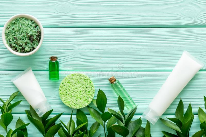 Organic cosmetic with herbs on mint green wooden background top view mock up stock photography