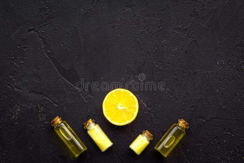 Organic cosmetic with lemon for homemade spa with oil and fresh fruit black background top view mock up stock image