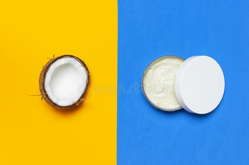Organic cosmetics with coconut oil, ripe coconut on yellow and blue colored background top view minimal flat lay style. Coconut stock photo