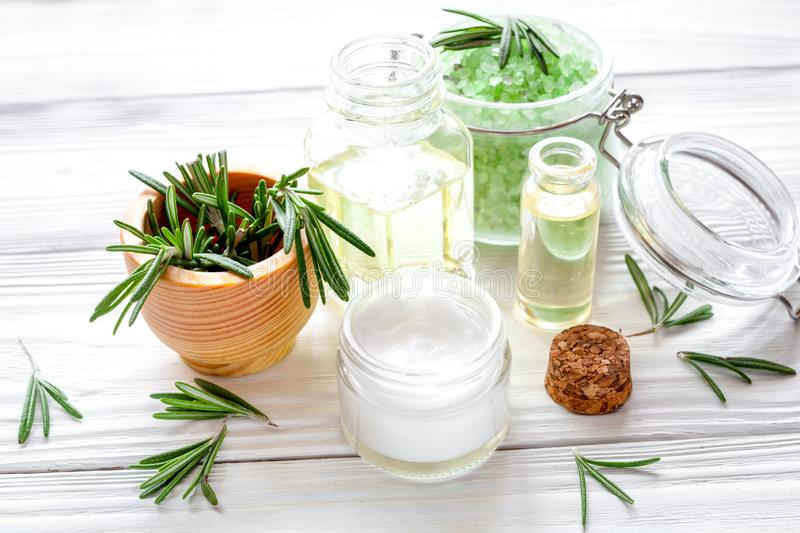 Organic cosmetics with extracts of herbs rosemary on wooden back stock photo