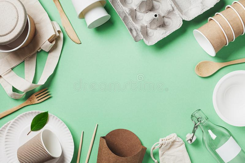 Organic cotton bag, glass jar and recycled tableware on green background top view. Zero waste, eco friendly, plastic free concept. stock photography