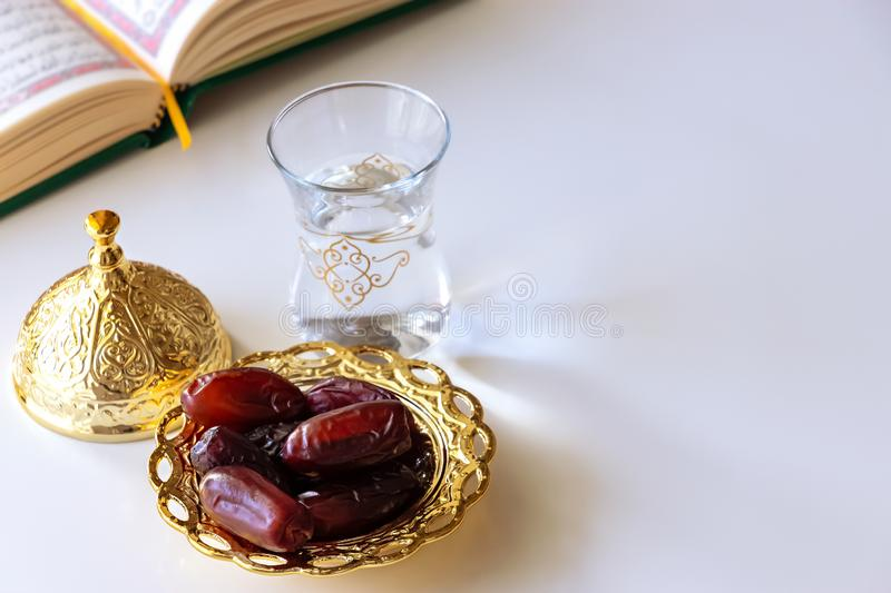 Organic Dates In Traditional Arabic Golden Plate, Cup Of Drinking Water And Quran Book. Ramadan Concept Stock Image - Image of islamic, month: 146577791