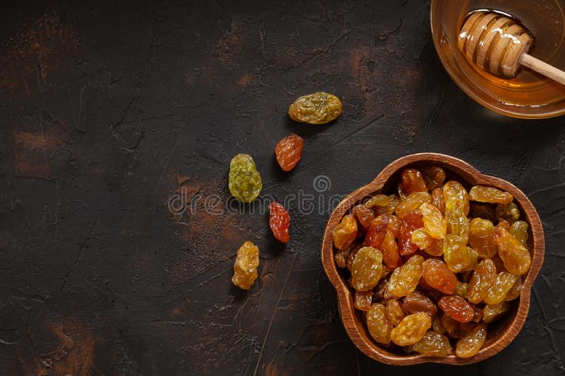 Organic dried golden raisins in wooden bowl and fresh honey royalty free stock photo