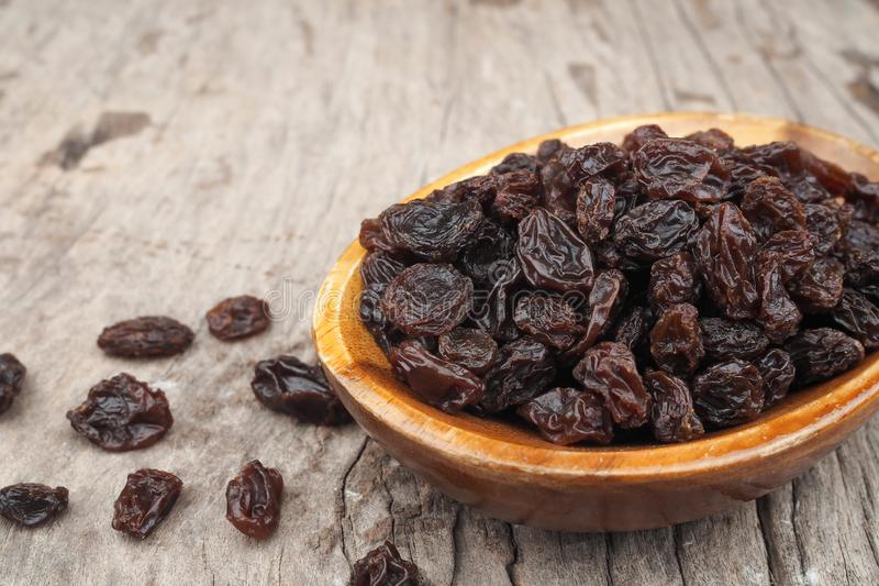 Organic dried Raisins in wood bowls on old wooden table, Currant. In wood dish royalty free stock photos