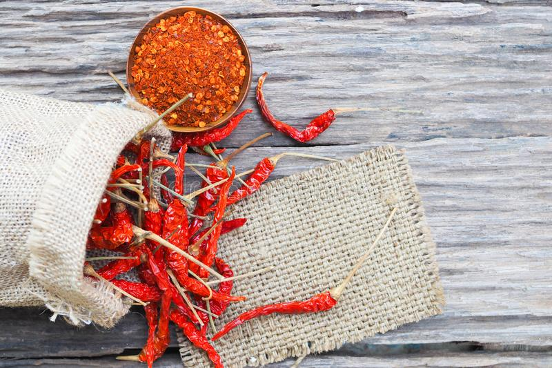 Organic dried red hot peppers on old wooden table, Cayenne pepper in wood bowl stock image