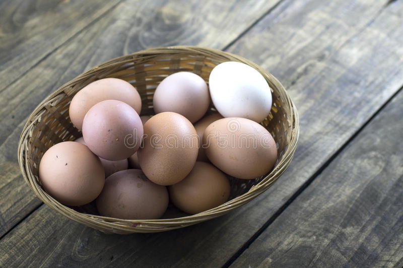 Organic eggs in basket. On wooden table stock images