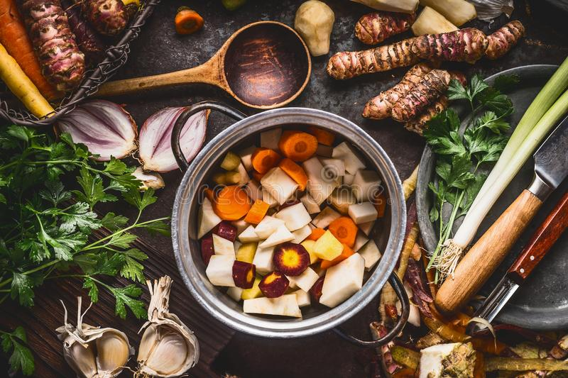 Organic farm vegetables cooking and eating. Cooking pot with diced colorful root vegetables on rustic kitchen tables background wi royalty free stock photos