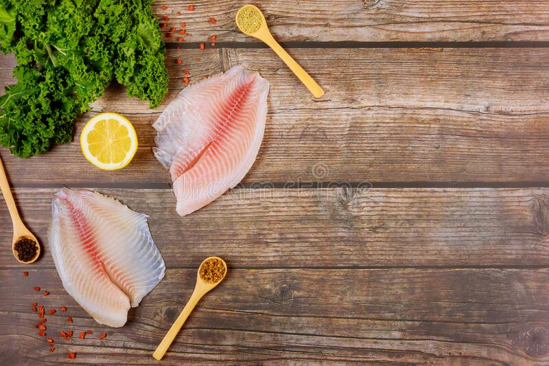 Raw tilapia fillets with seasonings over wooden background royalty free stock photos