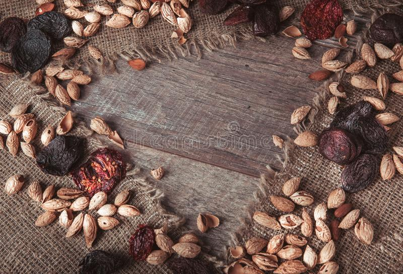 Organic food amonds, raisins, dried apricots, dried tomatoes, prunes, dried fruits in wooden desk. Food mix background, top view, stock image