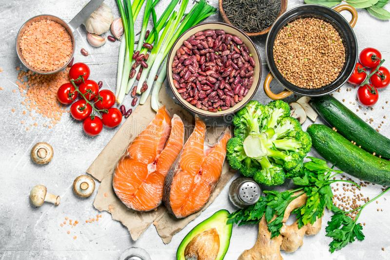 Organic food. Assortment of heathy food with raw salmon steaks. On a rustic background royalty free stock photo