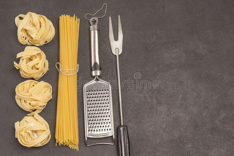 Organic food  on black background. Variety of types and shapes of dry Italian pasta with. Grater and  fork. Top view, copy space royalty free stock image