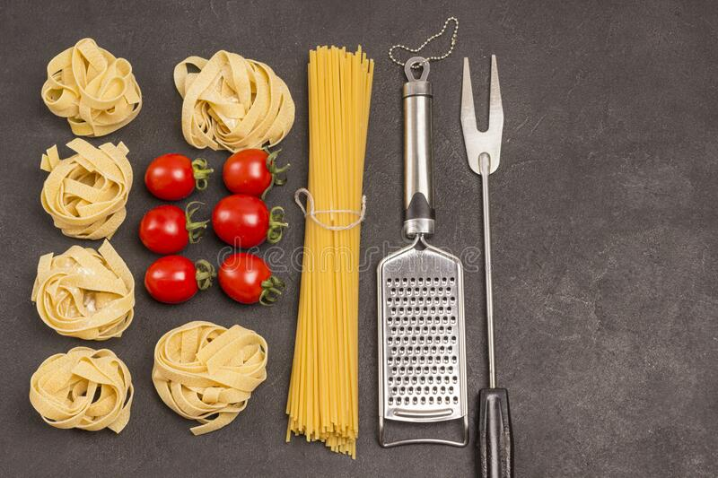 Organic food  on black background. Variety of types and shapes of dry Italian pasta with vegetables tomatoes, red peppers, garlic. Parsley. Grater and  fork royalty free stock photo