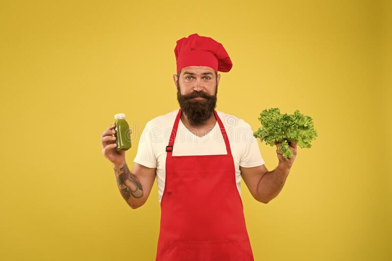 Organic food. cook hold fresh and blended salad smoothie bottle. organic eco vegan products. bearded man chef in apron. And hat. hipster make vitamin summer royalty free stock photo