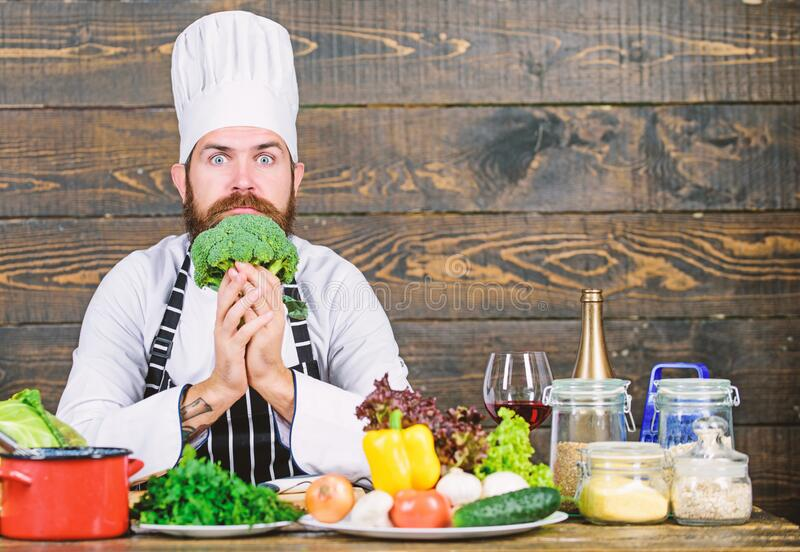 Organic food. Fresh ingredients only. Culinary recipe concept. Man bearded hipster cooking fresh vegetables. Freshest stock image