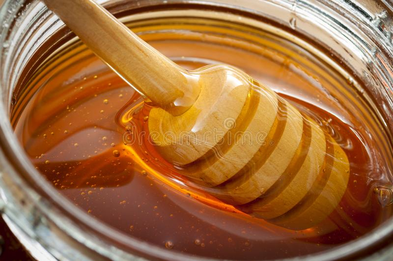 Organic food and healthy diet concept with a macro close up on a wood honey dipper or drizzler pouring aromatic honey into a glass stock photos