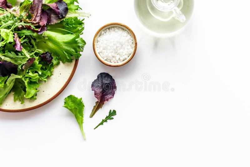 Organic food pattern with green and red salads mix and oil white background top view space for text stock photography