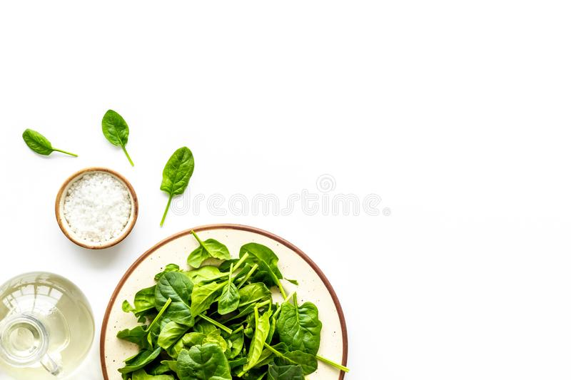 Organic food pattern with green salads mix and oil white background top view space for text stock image