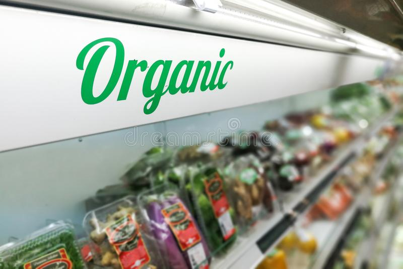 Organic food signage on modern supermarket fresh produce vegetable aisle stock image