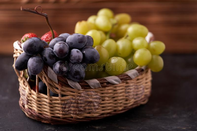 Organic fresh berries of green grapes, strawberries, raspberries, blue blueberries in a basket on a dark concrete background. stock photo