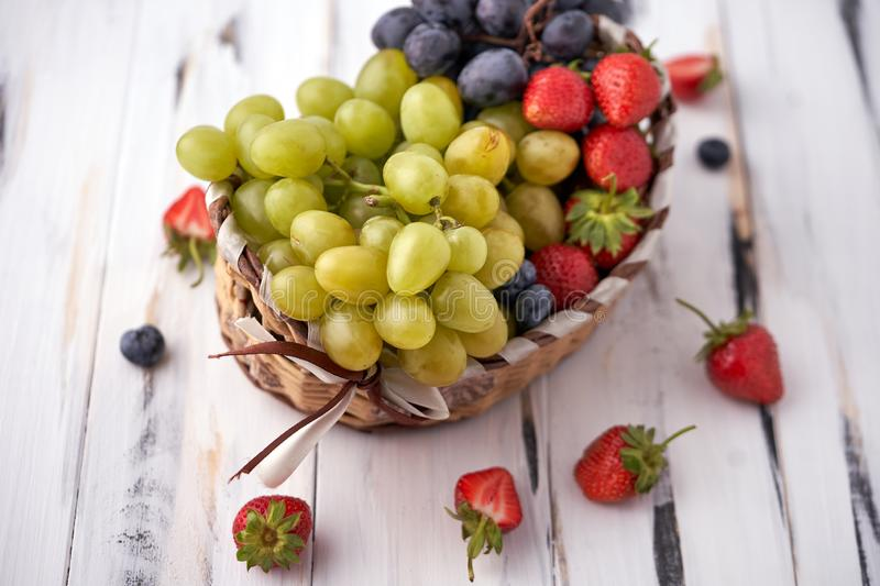 Organic fresh berries of green grapes, strawberries, raspberries, blueberries in a basket on a light wooden background. stock photography