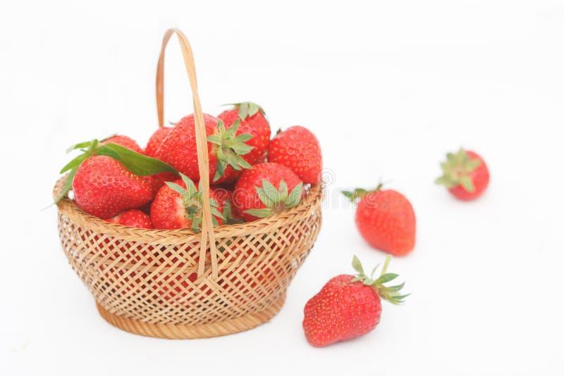 Organic, fresh strawberries in wicker basket on white background royalty free stock photo
