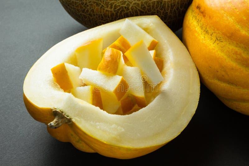 Organic fresh yellow melon slices on black background royalty free stock photography