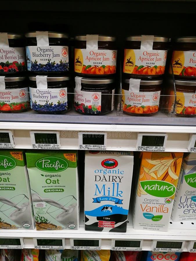 Organic fruit jam and dairy milk, supermarket shelf stock images