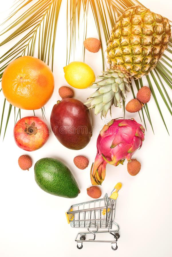 Organic fruits falling into mini shopping cart. Organic market concept. Exotic tropical fruits on white background. Grocery. Shopping cart royalty free stock photo