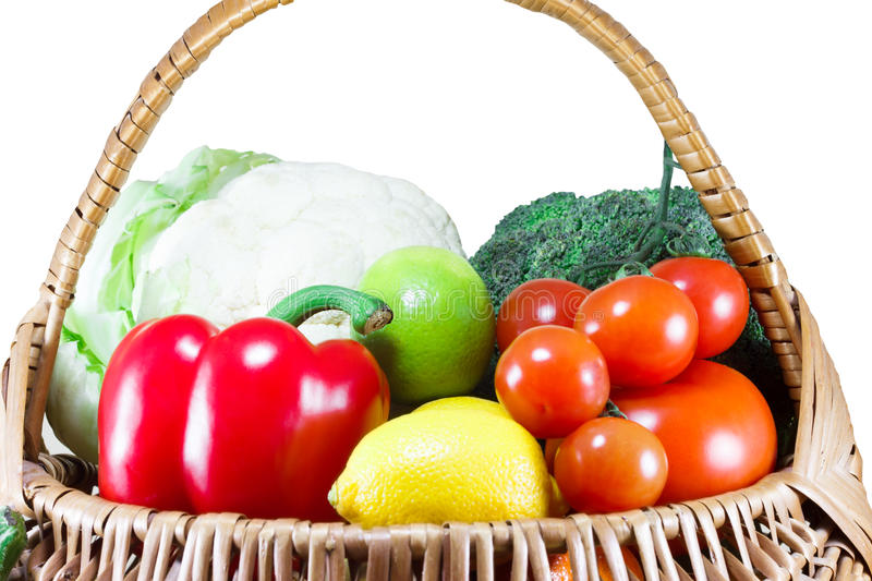 Organic fruits and vegetables in a wicker basket royalty free stock photo