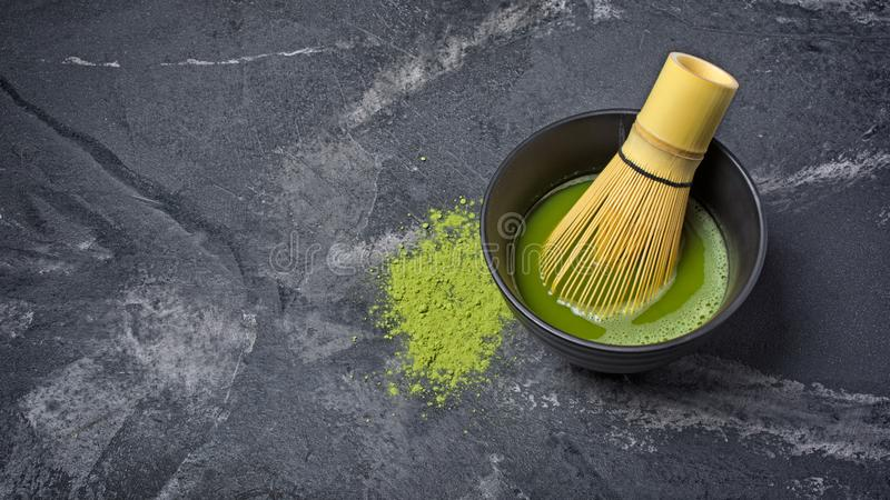 Organic green matcha tea in black ceramic cup with bamboo whisk. Organic green matcha tea in ceramic cup with bamboo whisk on black marble background with copy stock photography