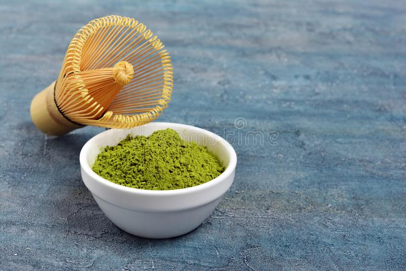Organic green matcha tea�powder with bamboo whisk on blue concrete background. Organic green matcha tea�powder in white bowl with bamboo whisk on blue royalty free stock image