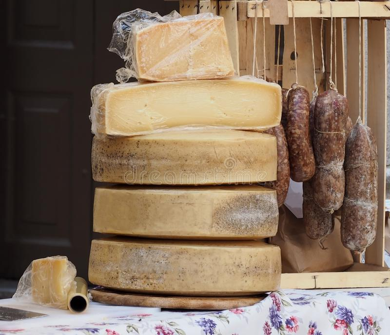 Organic hard cheese wheels stacked and salami hanging, on a shelf of an outdoor rural market in northern Italy stock image