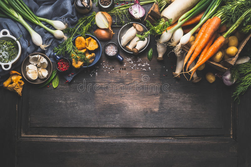 Organic harvest Vegetables from garden and forest mushrooms. Vegetarian ingredients for cooking on dark rustic wooden background. Top view, border royalty free stock image