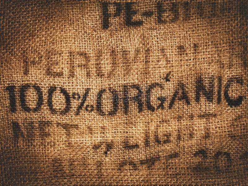 Organic hessian coffee bag. Background of a hessian coffee bag stamped and certified one hundred percent organic royalty free stock image