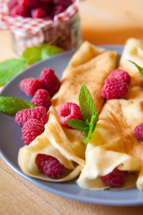 Organic home made Crepes with cream and raspberry. French thin delicious crepes made from eggs milk, flour and vanilla esence, traditional recipe in many french royalty free stock photography