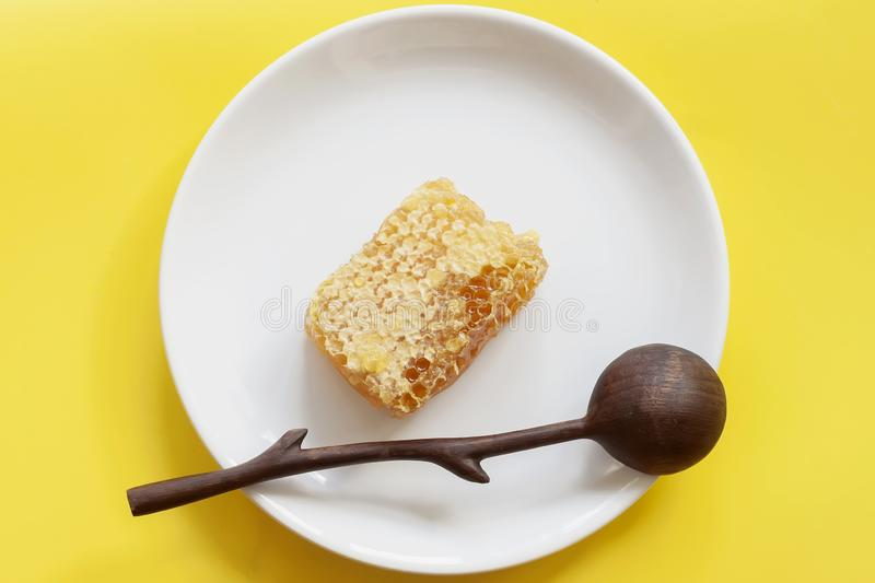 Organic honeycombs, wooden spoon in white plate, yellow background. Natural ingredients, bee products for food concept. Organic honeycombs, wooden spoon in white royalty free stock photo