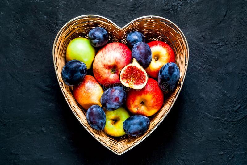 Organic Jedzenia pojęcie Czerwoni jabłka, śliwki i figi w słomianej wazie robić w postaci serca na zmroku, - błękitny tło zdjęcie stock