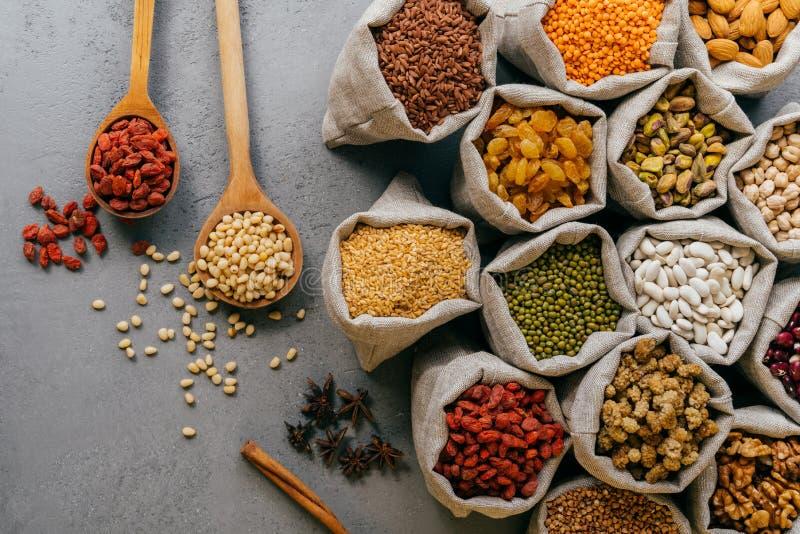 Organic Jedzenia poj?cie Odżywczy składniki w burlap grabiją, gwiazdowy anyż, rozlewający cerelas od łyżek na popielatym tle obrazy stock