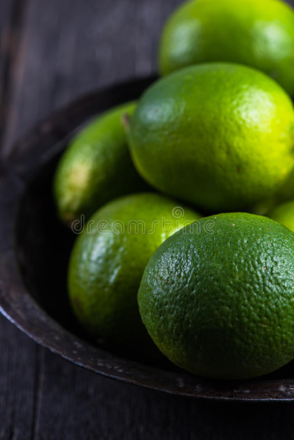 Organic limes on table. Organic limes on wooden rustic table royalty free stock photos