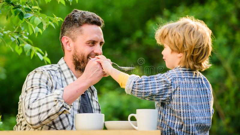 Organic and natural food. small boy child with dad. they love eating together. Weekend breakfast. father and son eat. Outdoor. healthy food. Family day bonding stock photography