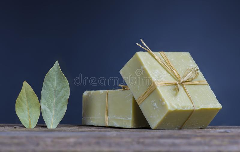 Organic natural handmade bay laurel soap with olive oil and leaves on wooden rustic backdrop royalty free stock images