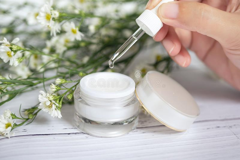 Organic natural skincare concept. open blank cosmetic cream jar with white cream texture inside and women hand holding dropper stock images
