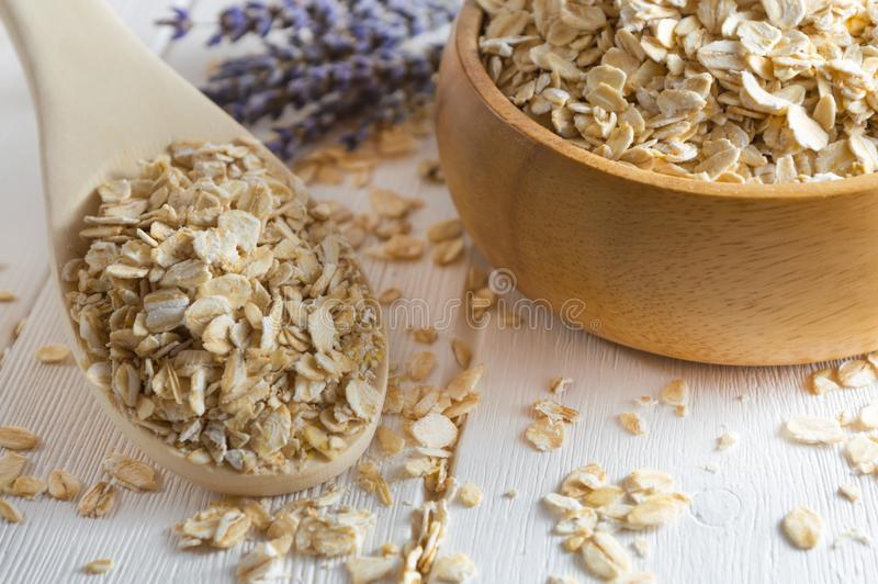 Organic oat flakes in wooden bowl and spoon stock photo