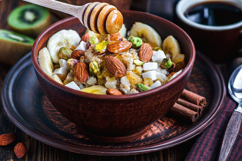 Organic oatmeal porridge with bananas, honey, almonds, pistachio, coconut, kiwi fruit, cinnamon, raisins in dark ceramic bowl stock images