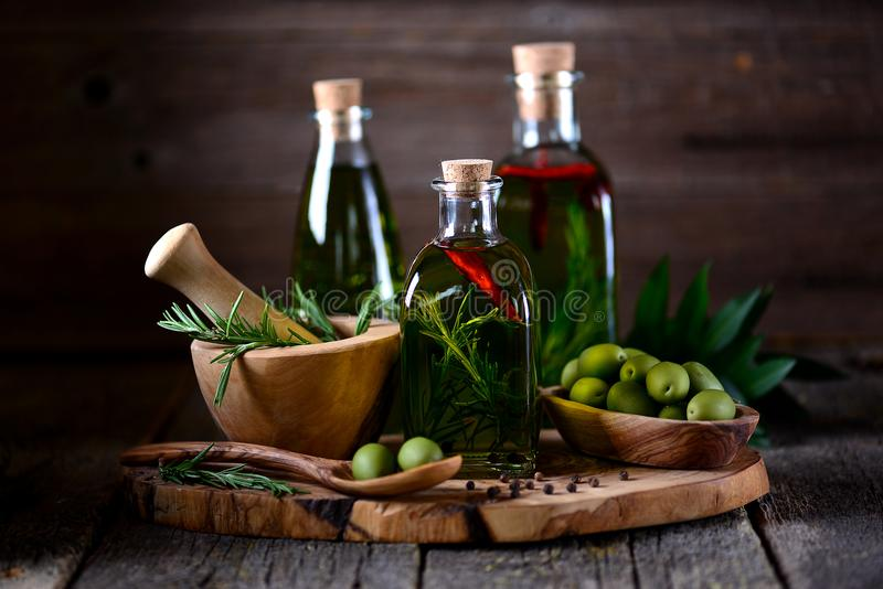 Organic olive oil with spices and herbs on an old wooden background. Healthy food. Food
