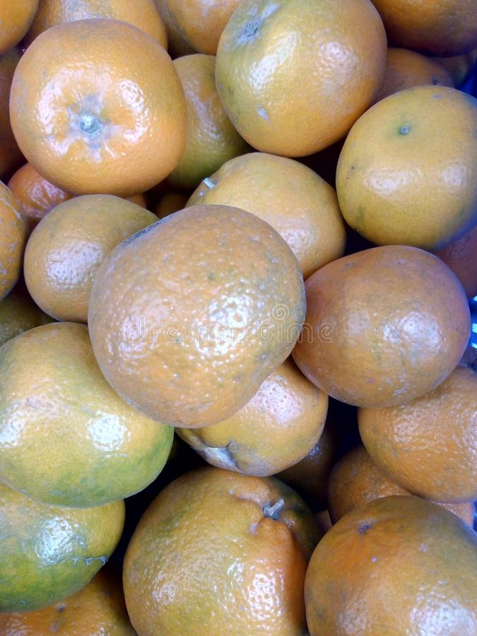 Close up view of fresh organic yellowish oranges arraged in fruit basket. Organic oranges arranged in fruit basket royalty free stock photography