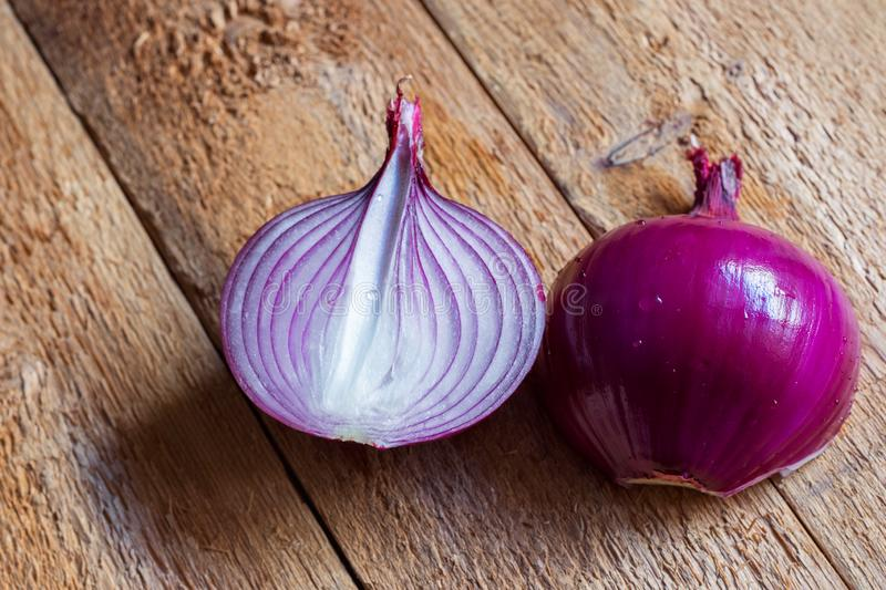 Organic peeled halved red onion bulb with water drops on weathered wood table. Rustic kitchen interior. Healthy food ingredients royalty free stock photography