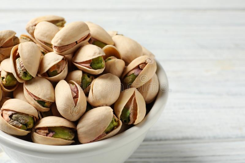 Organic pistachio nuts in bowl on wooden table, closeup. Space for text stock images
