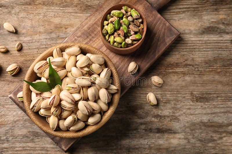 Organic pistachio nuts in bowl on wooden table. Space for text. Organic pistachio nuts in bowl on wooden table, flat lay. Space for text stock photo